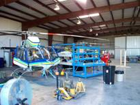 Helicopter being repaired inside hangar